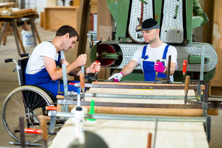 people with disabilities: disabled worker in wheelchair in a carpenters workshop with his colleague Stock Photo