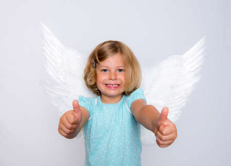 positiv: little blond girl with angel- wings and thums up Stock Photo