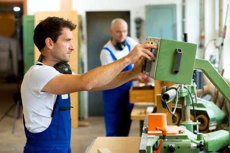 carpintero: trabajador en una carpintería de fábrica usando la máquina