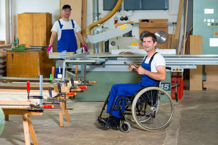 disabled worker in wheelchair in a carpenter's workshop with his colleague Foto de archivo