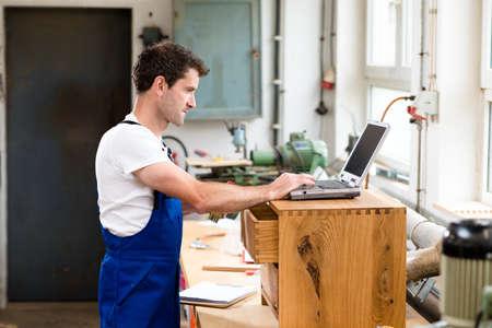 carpenter: worker in a carpenters workshop using computer