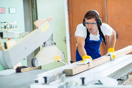 carpintero: trabajador en el taller usando la máquina de sierra de carpintero Foto de archivo