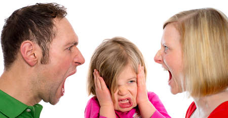 girl fighting: young man and  woman screaming in front of little girl Stock Photo