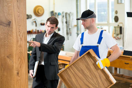 bib overall: boss and worker together in a carpenters workshop