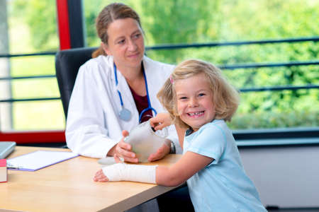 pediatrist: female pediatrician in white lab coat bandaging the arm of a little girl