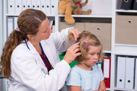 female pediatrician in white lab coat examined little girl
