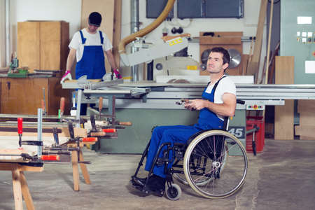 disabled worker in wheelchair in a carpenter's workshop with his colleague 版權商用圖片