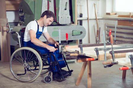 discapacitados: trabajador con discapacidad en silla de ruedas en el taller de un carpintero Foto de archivo