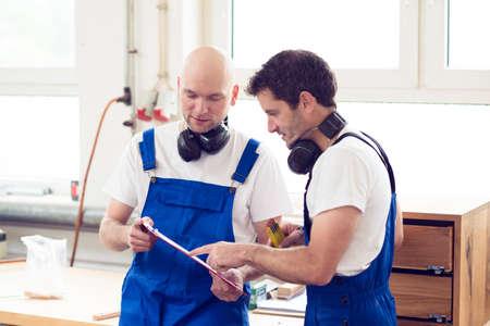 carpintero: de dos trabajadores en overoles azules en el taller de un carpintero Foto de archivo