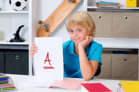 blond boy on desk with good report card Imagens - 45489357