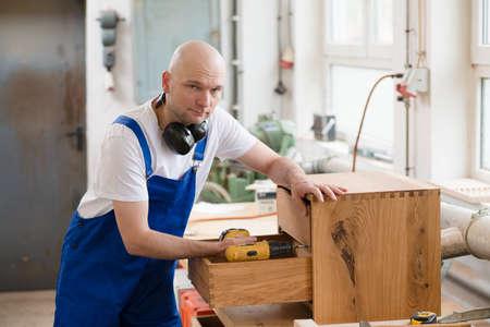 carpenter: worker in blue dungarees in a carpenters workshop