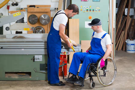 disabled: disabled worker in wheelchair in a carpenters workshop with his colleague Stock Photo
