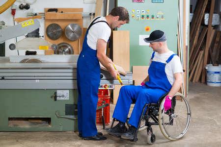 silla de ruedas: trabajador con discapacidad en silla de ruedas en el taller de un carpintero con su colega