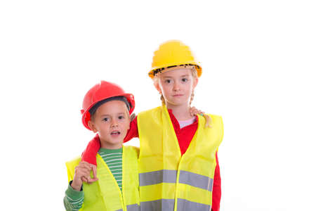 young worker: boy and girl with reflective vest and helmet in front of white background Stock Photo