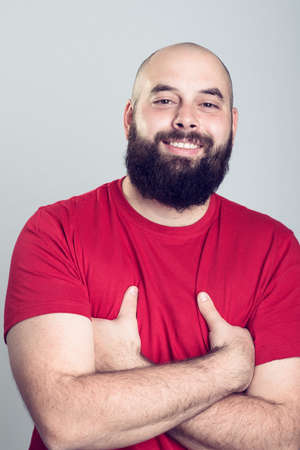 red shirt: young bearded man in red shirt in front of gray background
