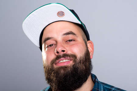 young bearded man with baseball cap is smiling