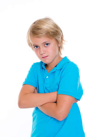 sternly: bearish blond boy with crossed arms in front of white background Stock Photo