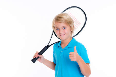 blond boy with tennis racket and thumb up in front of white background Stock Photo