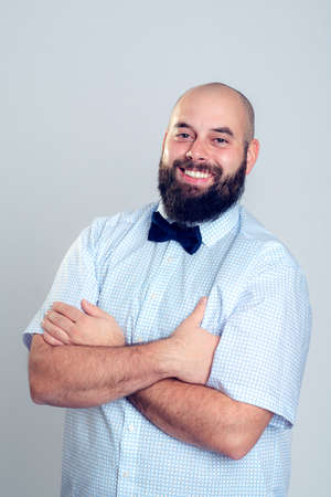 dapper: young smiling and bearded man in blue shirt and bow tie Stock Photo