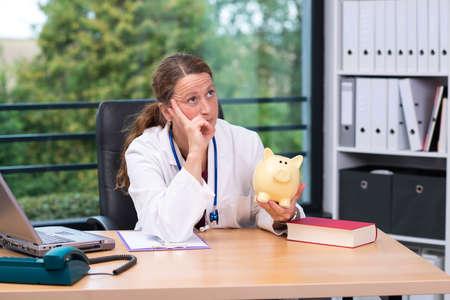 ganancias: joven doctora en su oficina con una alcancía