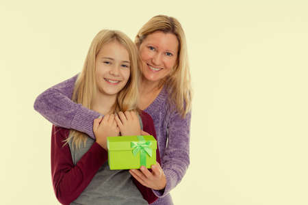 mothersday: blond girl and woman with a green gift box Stock Photo