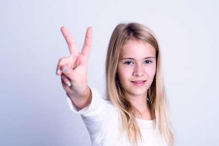 simbolo de la paz: bonita chica rubia en frente de fondo gris que muestra signo de la victoria Foto de archivo