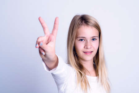 hand sign: nice blond girl in front of gray background showing victory sign