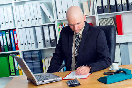 bald head: young businessman with bald head in the office is writing Stock Photo