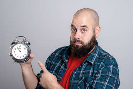 busy beard: young beardet man pointing to a clock