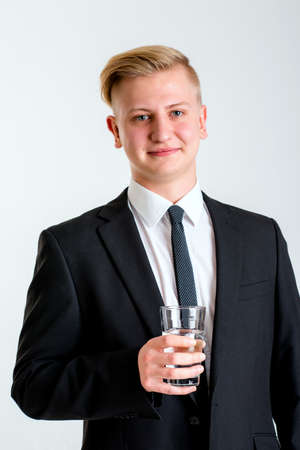 break from work: portrait of a young business man in black suit with water glass Stock Photo