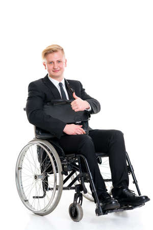 portrait of a young businessman in a wheelchair with thumb up