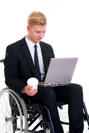 portrait of a young businessman in a wheelchair with computer and coffee mug