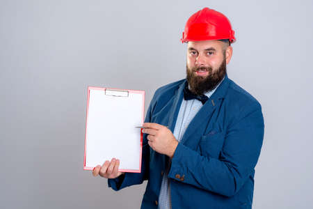 casco rojo: portrait of a young architect with red helmet and clipboard