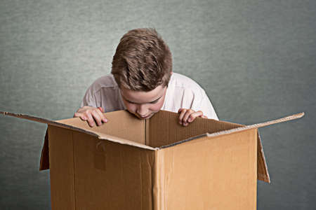 boy is looking in a big cardboard box Standard-Bild
