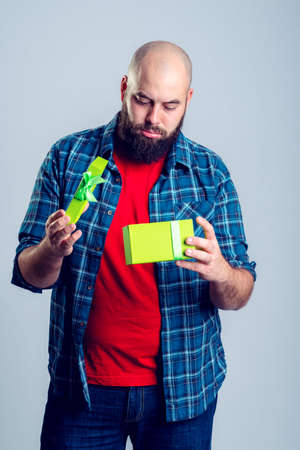 crestfallen: young frustrated man with green gift box Stock Photo