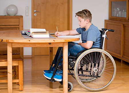 discapacitados: niño discapacitado en silla de ruedas haciendo los deberes
