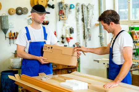 carpenter's bench: two men in workwear with cardboard in a carpenters workshop