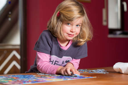 little blond girl doing a jigsaw puzzle 版權商用圖片