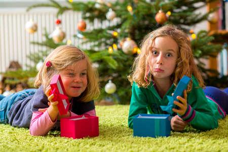 crestfallen: dos ni�as decepcionado con los presentes delante del �rbol de navidad