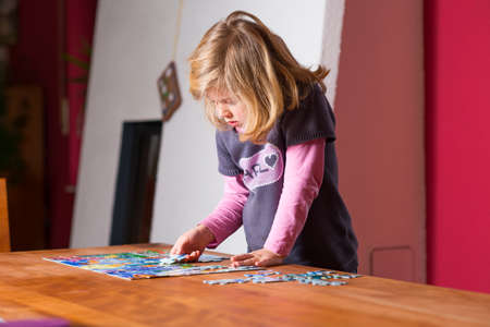 little blond girl doing a jigsaw puzzle Stock Photo