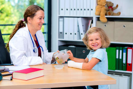 female pediatrician in white lab coat has candys for a little girl