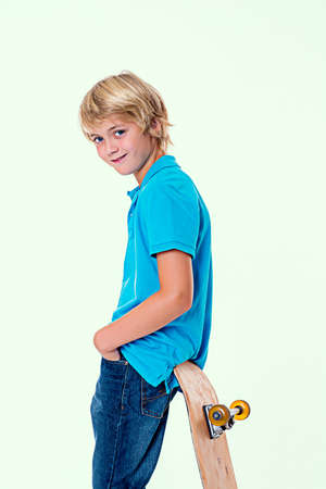 only one teenage boy: boy in blue dress with skateboard in front of white background