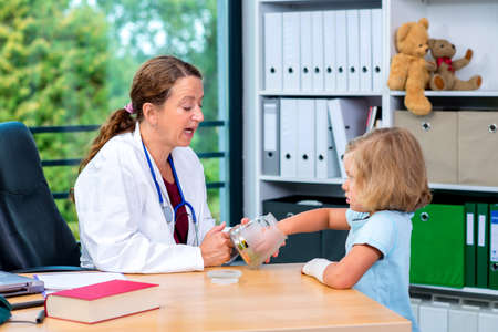 pediatrist: female pediatrician in white lab coat has candys for a little girl