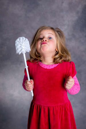 toilet brush: funny girl playing with toilet brush in front of gray background Stock Photo