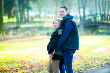 endearment: young pregnant woman with her husband in the park Stock Photo