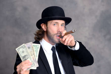 bowler hat: young businessman with bowler hat in black suit showing money and smoking big cigar