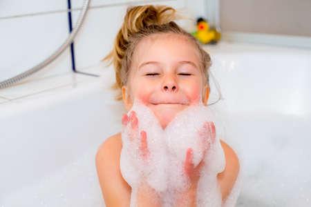 niños riendose: niña divertida con bañera de espuma en la bañera Foto de archivo