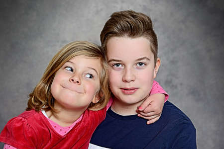 lighthearted: brother and sister together in front of gray background