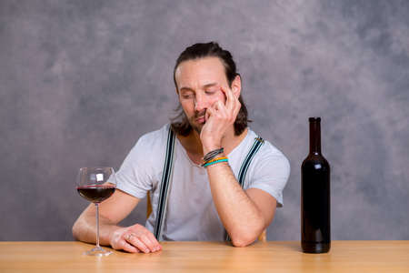 epicure: young man sitting bored at the table and drinking red wine Stock Photo
