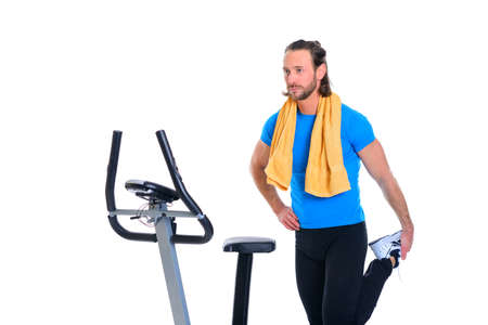 distension: young man in blue shirt warming up for train with fitness machine Stock Photo